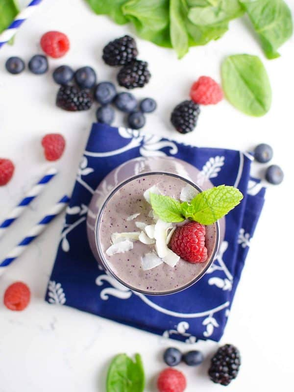 berry blast smoothie on a napkin with berries scattered round it.
