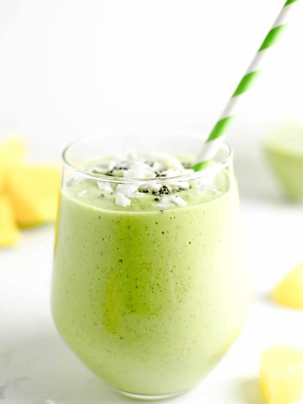 tropical green smoothie in a glass garnished with coconut chips and chia seeds.