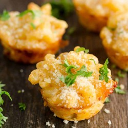lobster mac and cheese bites sitting on a platter garnished with fresh parsley