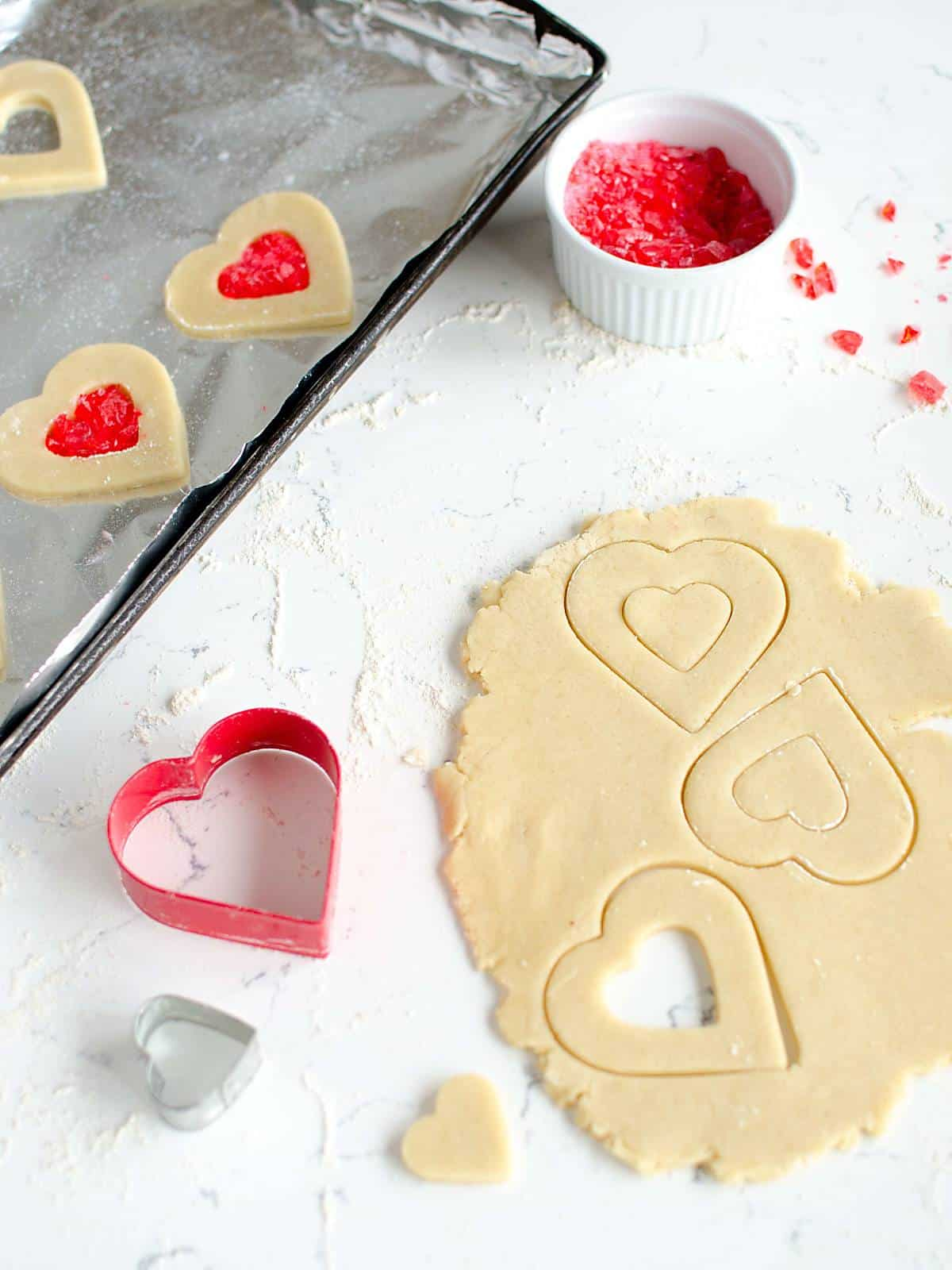 rolled cookie dough with heart shaped cookie cut outs, cookie cutters, and crushed red candy