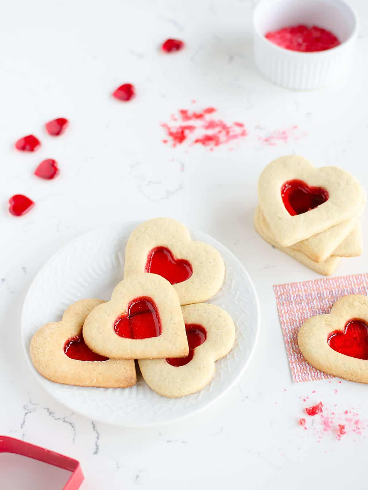 plate of heart shaped Valentines Day sugar cookies that have a red 'stained glass window' in the center