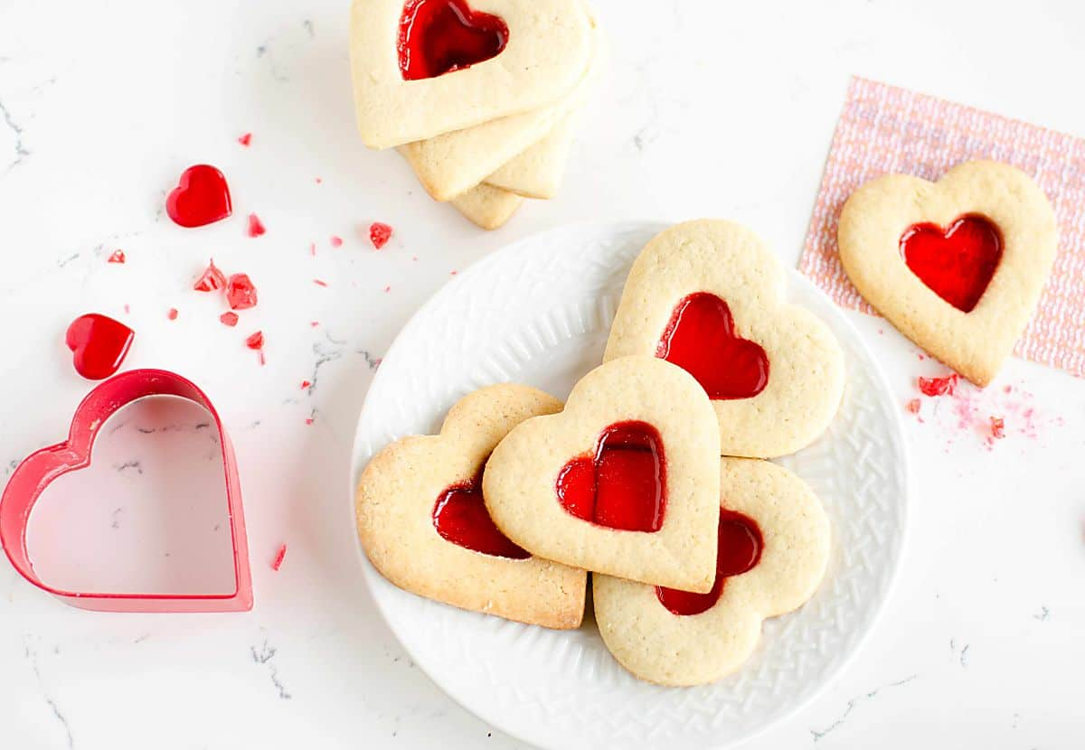 Valentine De-Coder Cookies, plate of heart shaped cookies with a red hard candy center, coded message and cookie cutter.