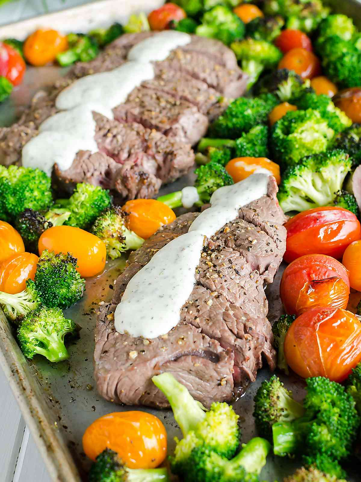2 cooked steaks on a half sheet pan surrounded by broccoli and red, orange and yellow grape tomatoes, topped with a homemade boursin cheese sauce