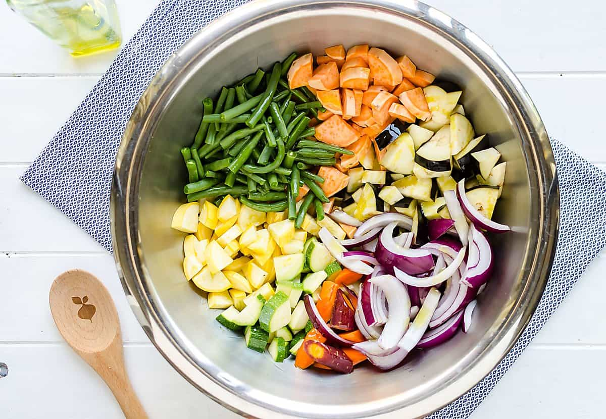 sections of cut up vegetables in a stainless steel bowl, sweet potatoes, green beans, summer squash, zucchini, carrots, red onions, eggplant