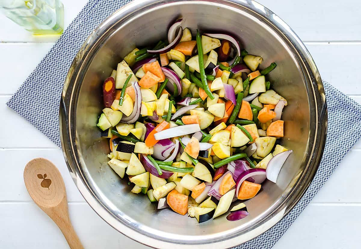 stainless steel bowl of mixed cut up vegetables including eggplant, sweet potatoes, zucchini, summer squash, green beans, red onions, rainbow carrots