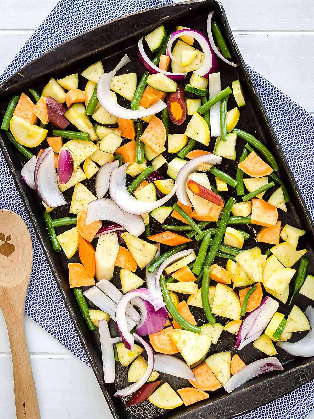 sheet pan full of cut up raw colorful vegetables with a wooden spoon on the side