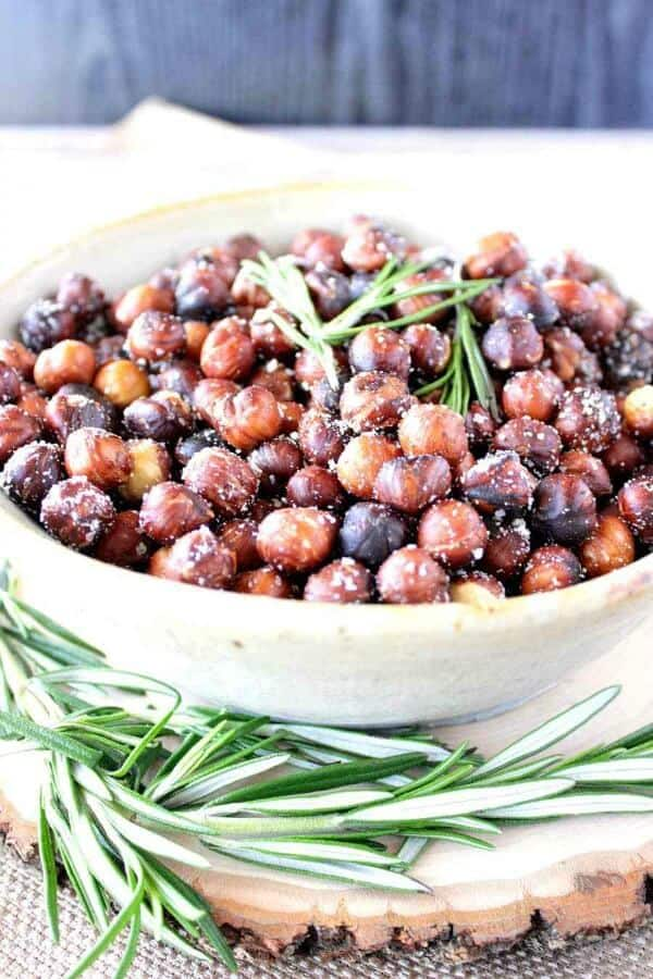 bowl of roasted hazelnuts with parmesan cheese, garnished with rosemary