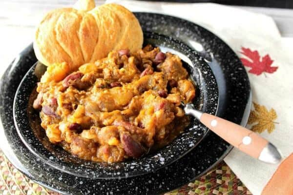 black bowl of smoky butternut squash chili with a pumpkin shaped biscuit