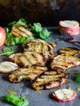 apple cider grilled pork chops with a stack of grilled apple slices