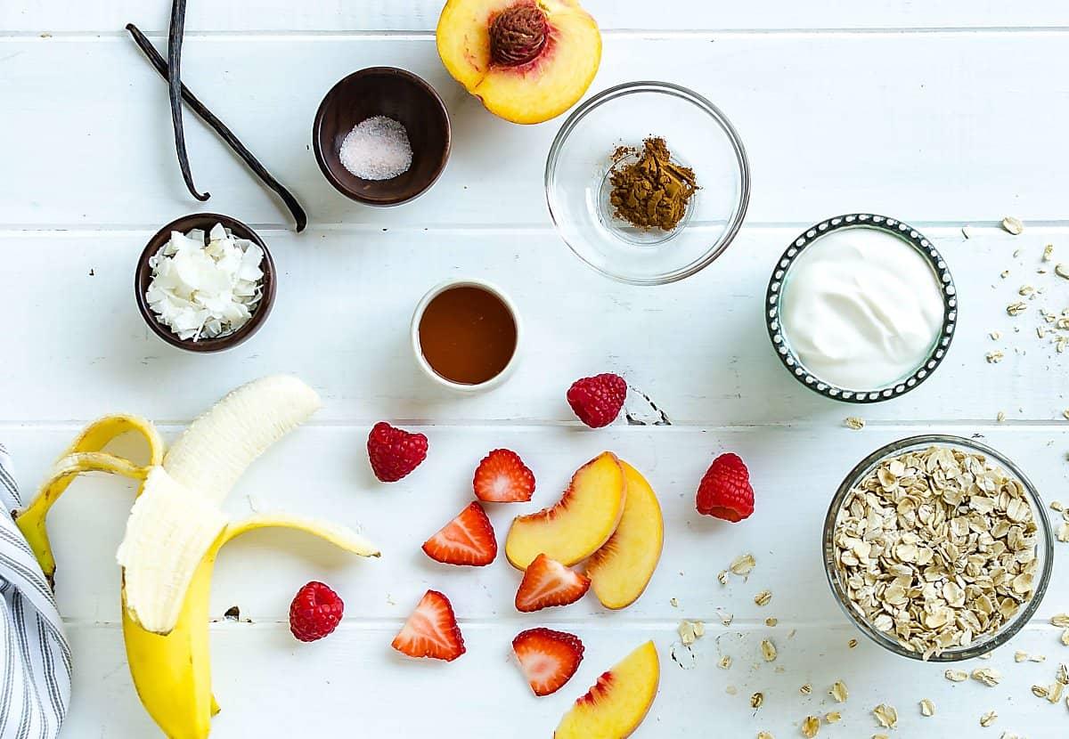ingredients for breakfast granola cups: banana, coconut flakes, vanilla bean, salt, cinnamon, honey, yogurt, rolled oats, sliced strawberries, sliced peaches, raspberries