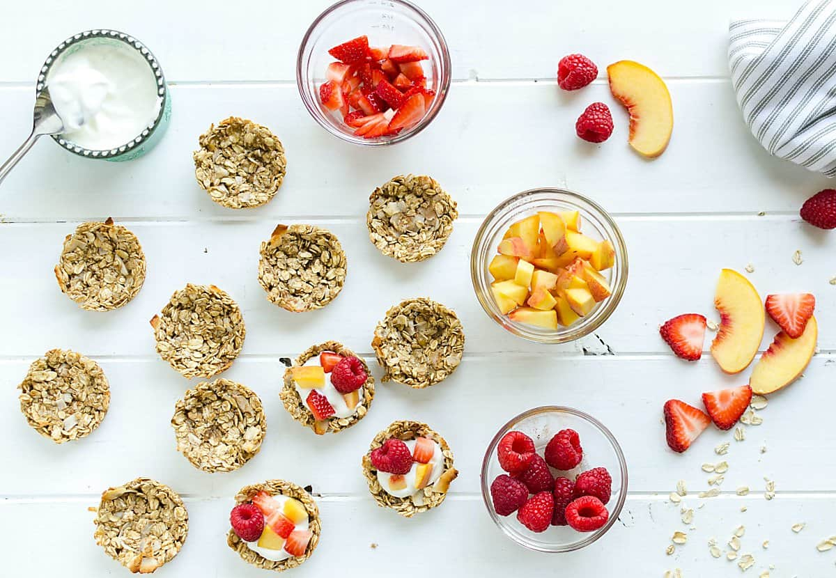 a group of coconut granola cups, some empty, some filled with yogurt, peaches, strawberries and raspberries. small bowl of yogurt on the side, small bowl of each of the fruits on the side