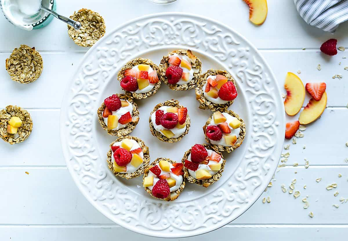 white round platter of coconut granola cups filled with yogurt, peaches, and raspberries. a few cups not filled yet, sliced peaches on the side