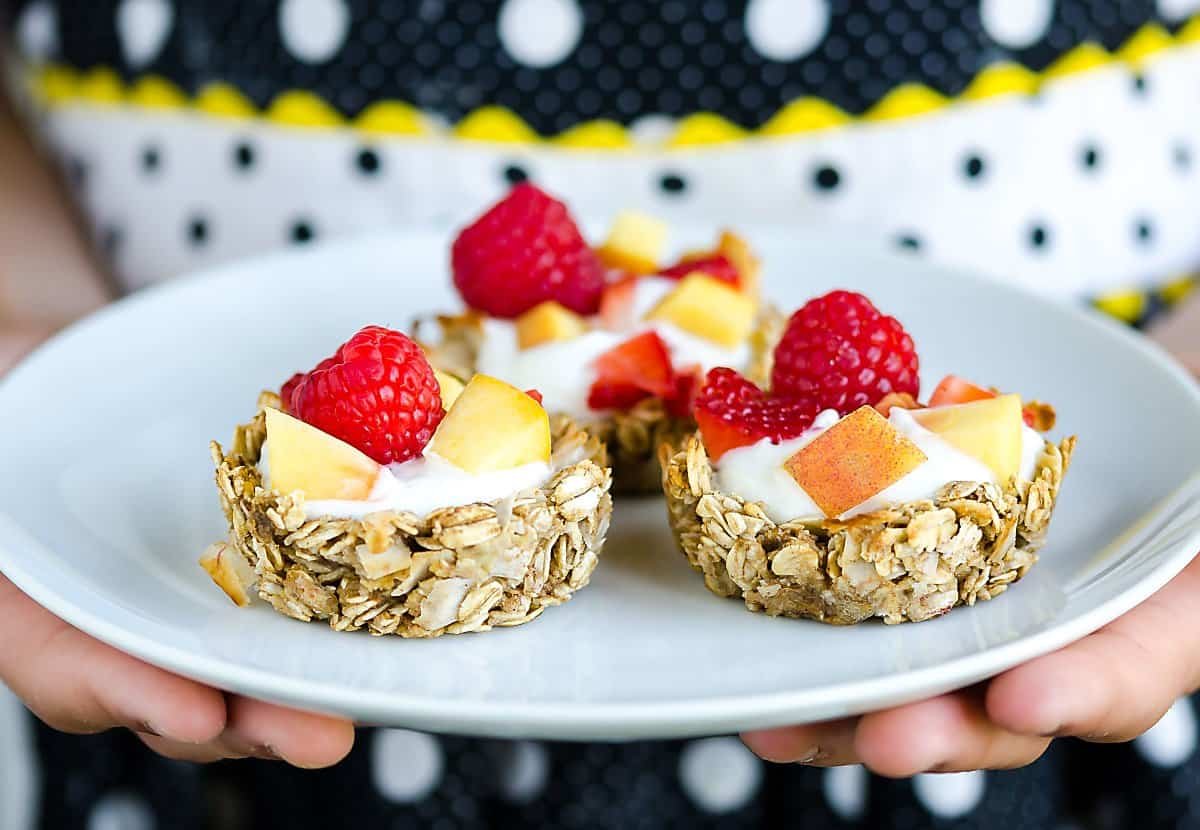 three homemade granola cups filled with yogurt, peaches and raspberries on a plate being held by someone in a polka dot apron