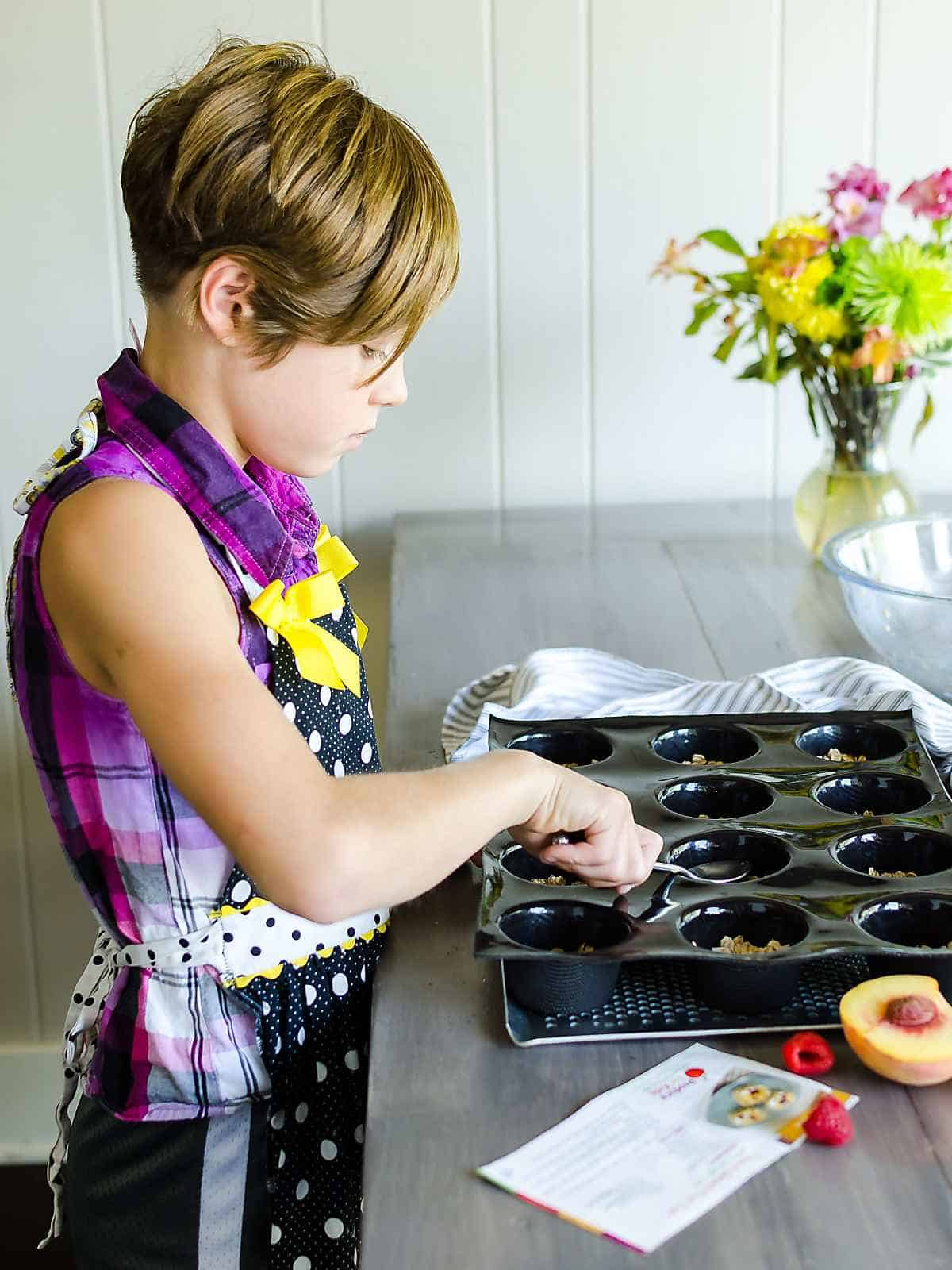 young girl pressing granola mixture into a black muffin tray