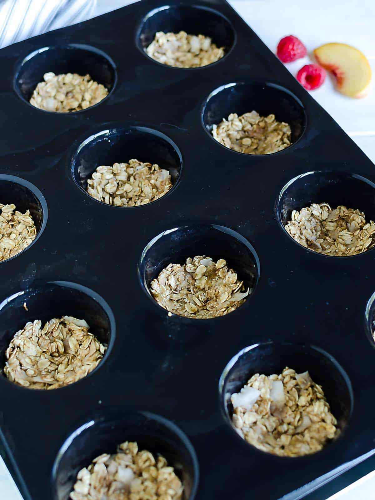 black muffin tray filled with homemade granola pressed into each well to form a mini cup