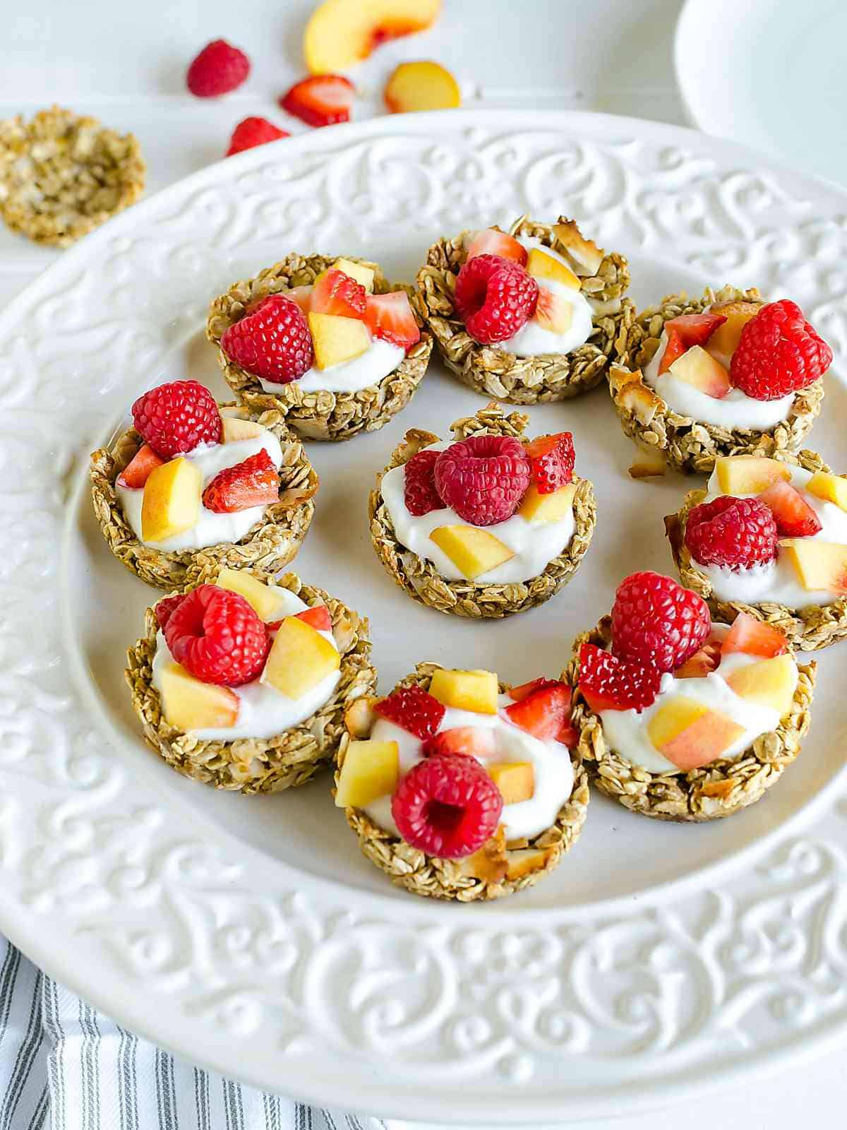 white platter of coconut granola cups filled with yogurt, peaches and raspberries