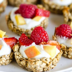 granola cup filled with yogurt, peaches, strawberries and rasbperries