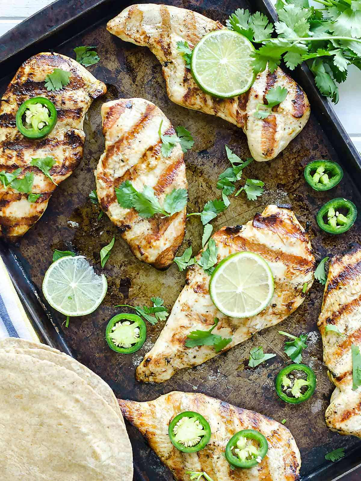 grilled garlic lime chicken breasts garnished with jalapeno , lime slices, and cilantro