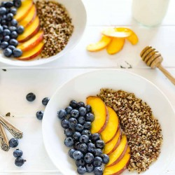 two quinoa and fruit breakfast bowls, blueberries and peaches and quinoa is arranged in rows, 2 spoons off to the side, a few blueberries and peach slices on the table and a honey dipper