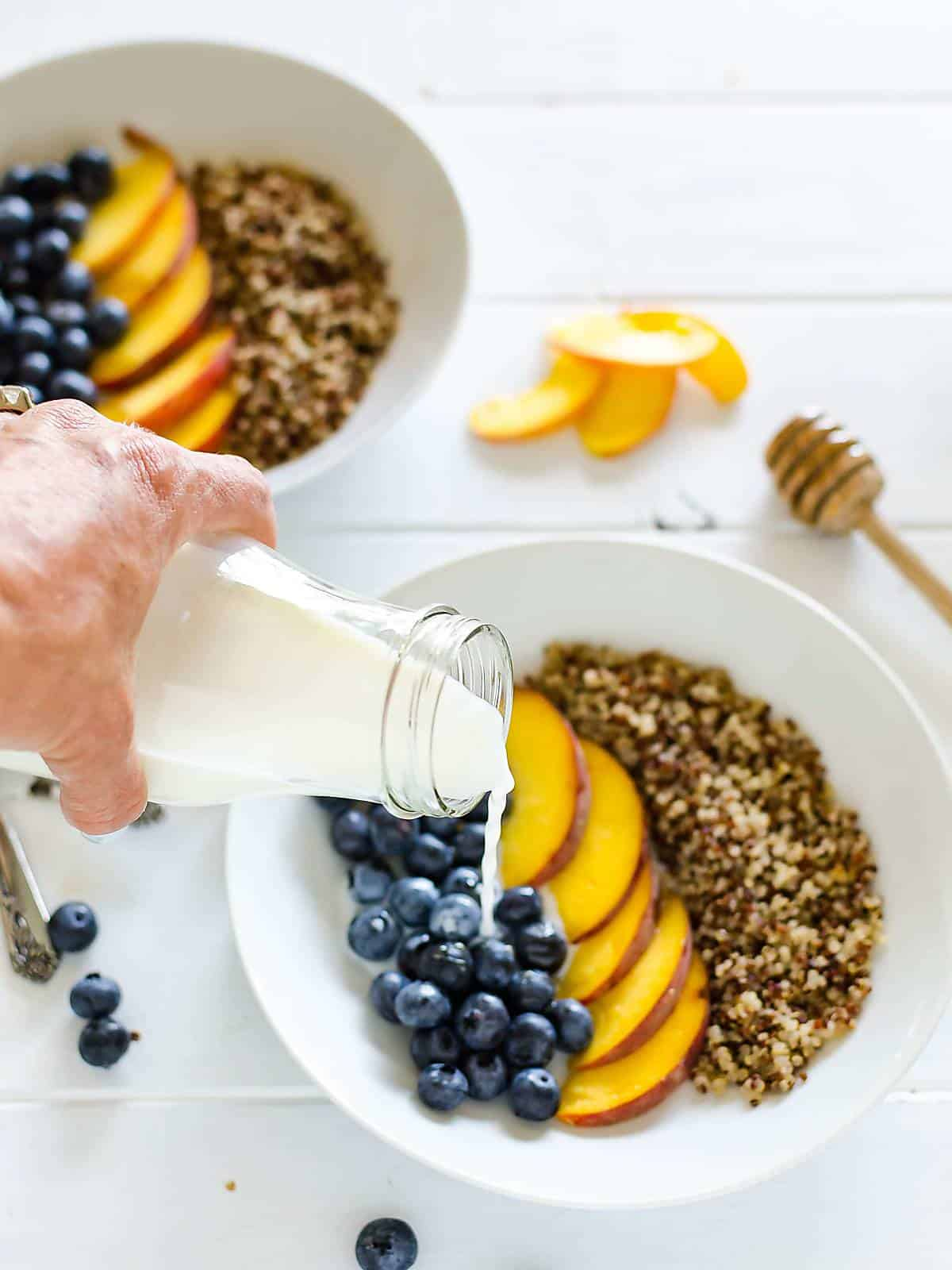 a hand pouring milk over a bowl of blueberries, peaches, and quinoa. another bowl in the back ground, a few sliced peaches on the table and a honey dipper