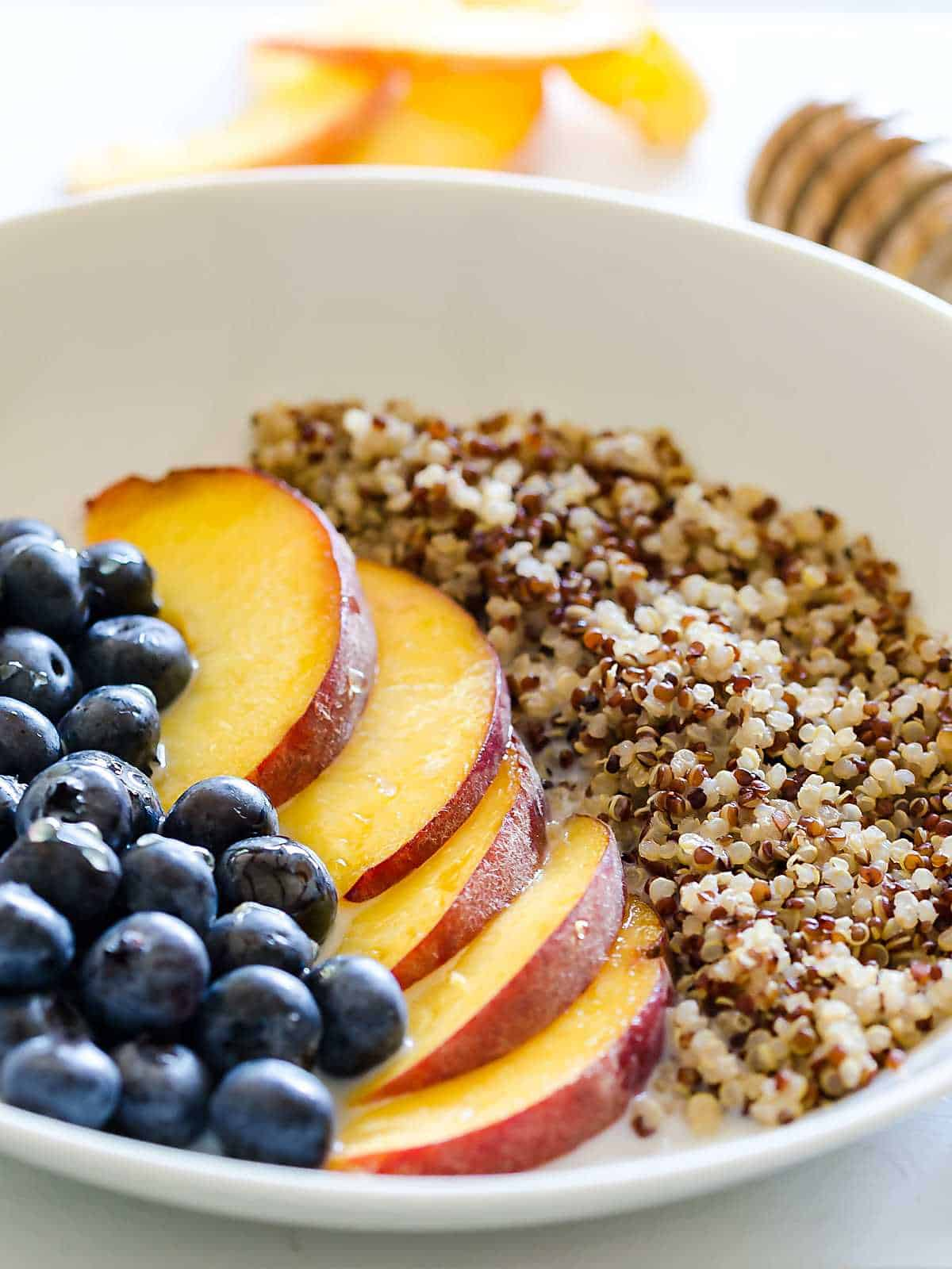 quinoa blueberries and peaches in a shallow white bowl, a row of each.