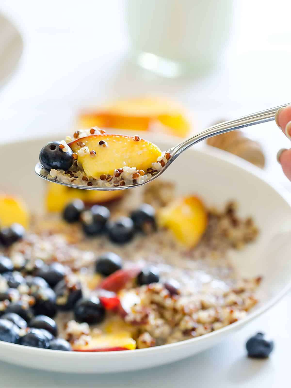 a spoon with quinoa, blueberries, a peach and milk being held above a bowl of quinoa and fruit and milk