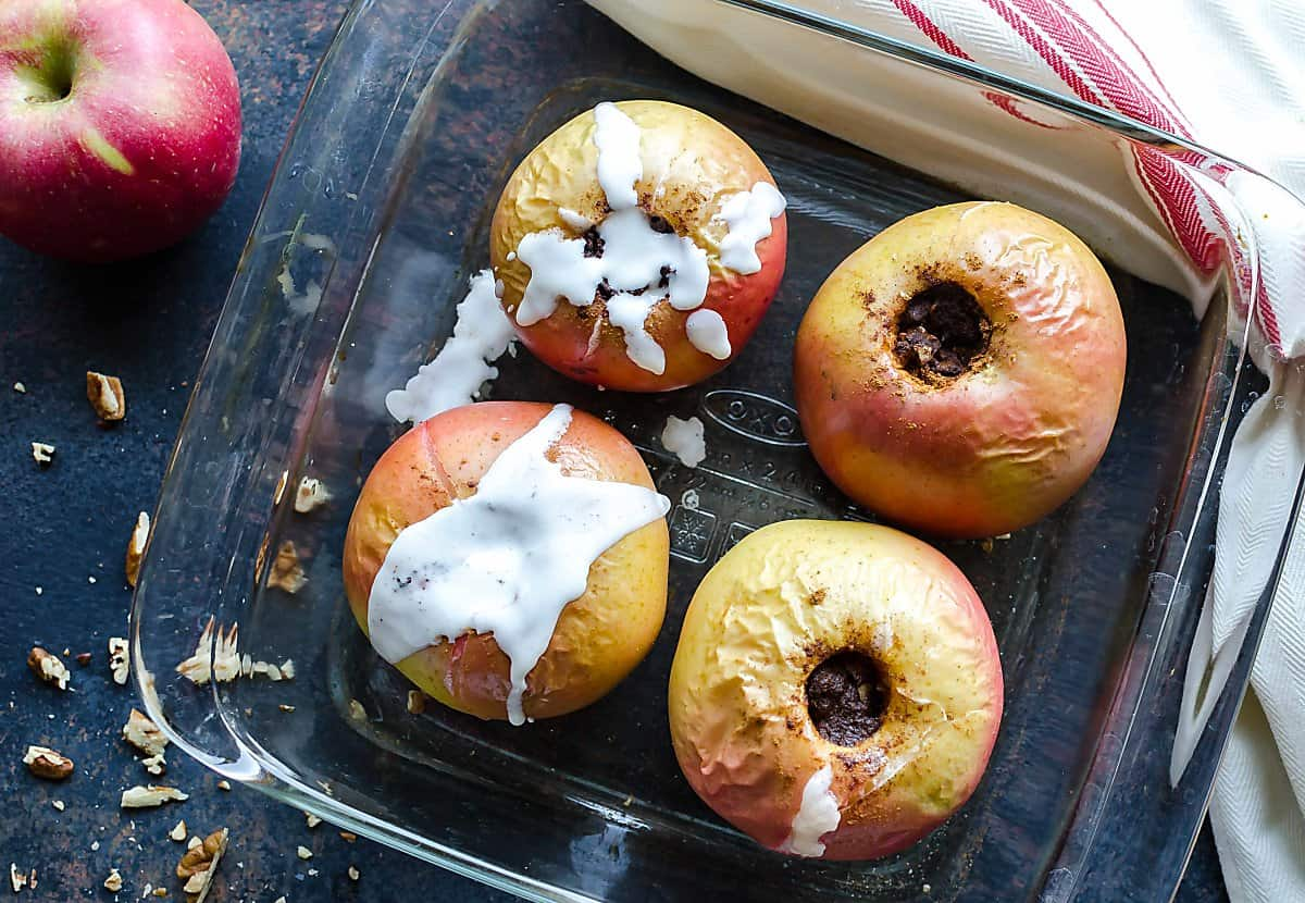 Top view of 4 healthy baked apples stuffed with pecans and cinnamon, 2 are drizzled with creamy yogurt sauce