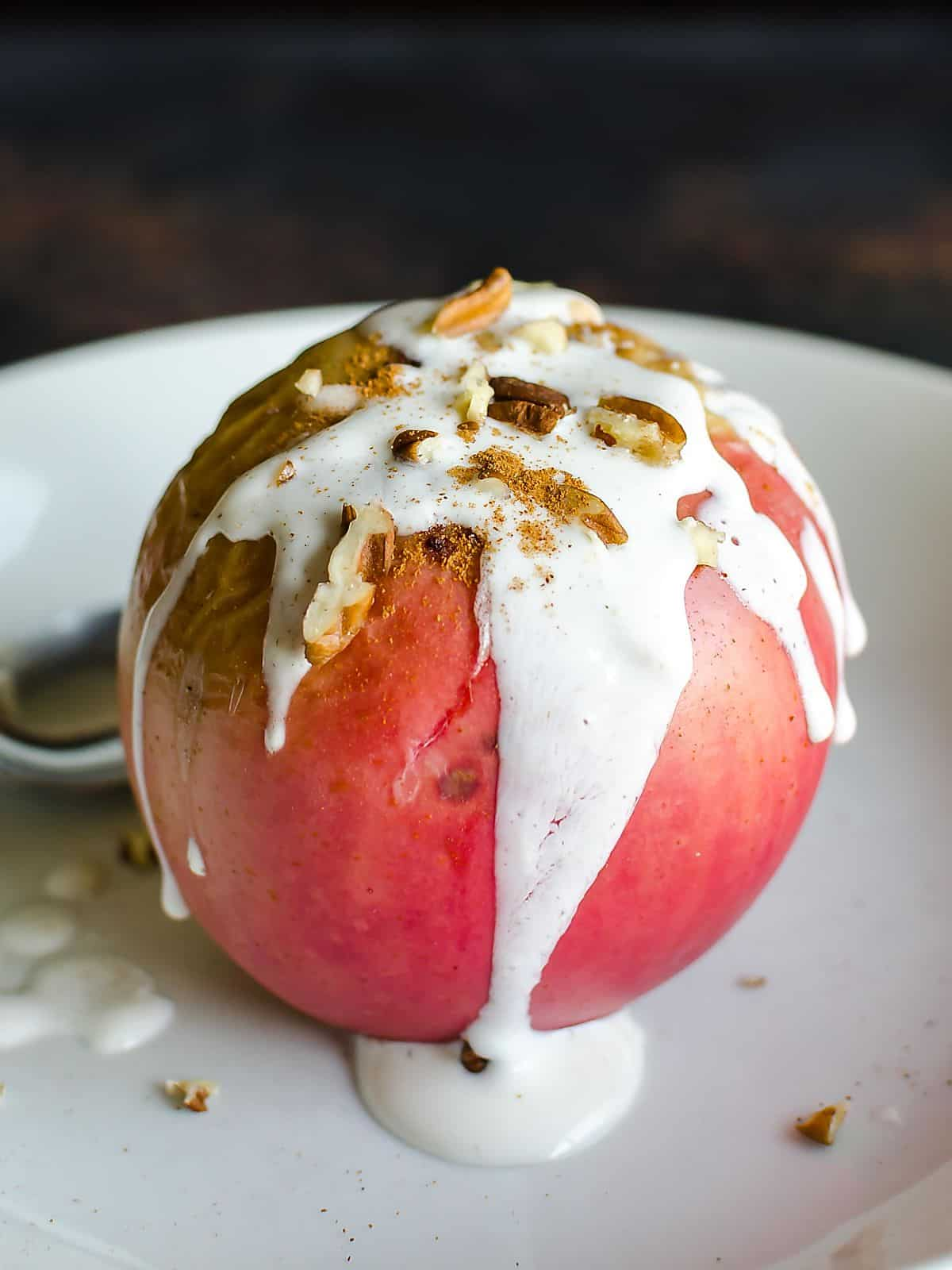 Healthy baked apple with creamy yogurt sauce dripping down the sides and topped with chopped pecans