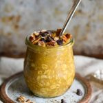 pumpkin overnight oats garnished with pecans and chocolate chips