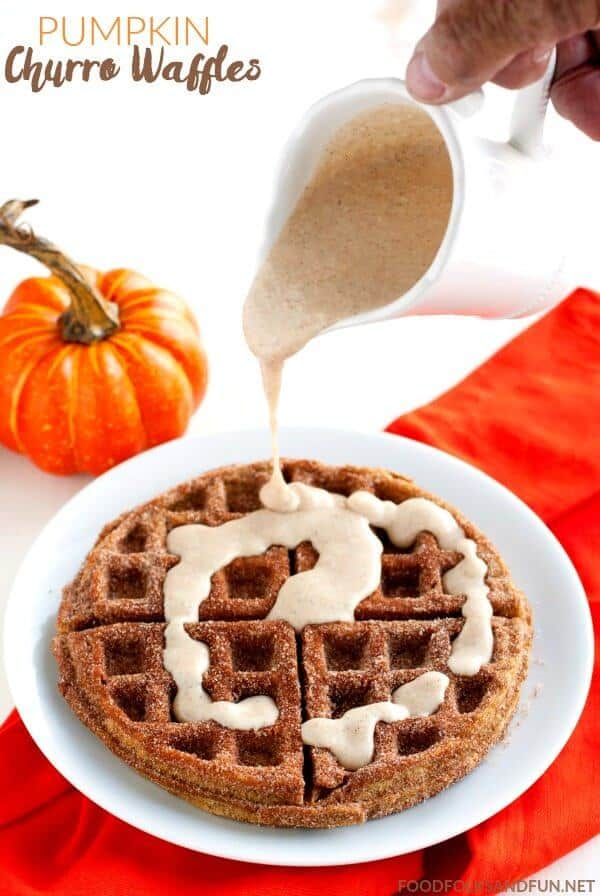 pumpkin churro waffle on a plate with spiced cream cheese glaze being poured on it.