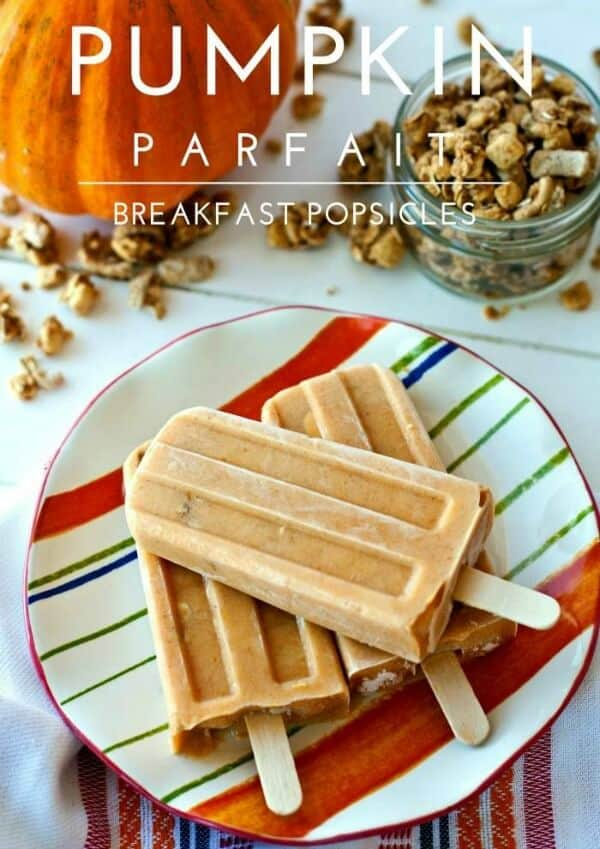 3 pumpkin parfait breakfast popsicles on a plate surrounded by a pumpkin and granola