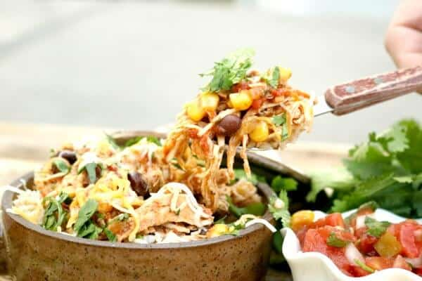 Fork lifting out a serving of chicken burrito bowls recipe from a brown bowl with salsa on the side