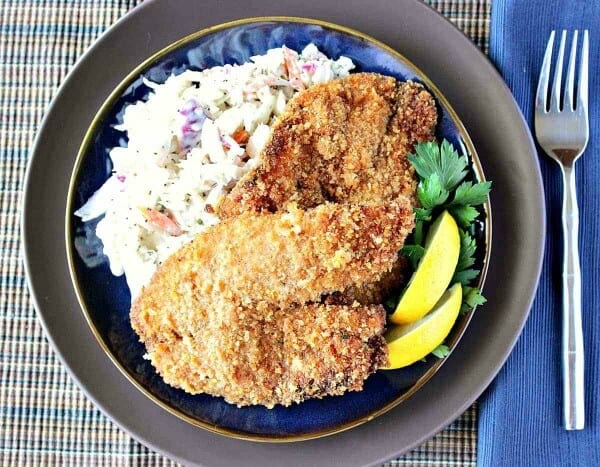 plate of fried tilapia on rice and garnished with lemon and parsley, good for meal plan october week 4