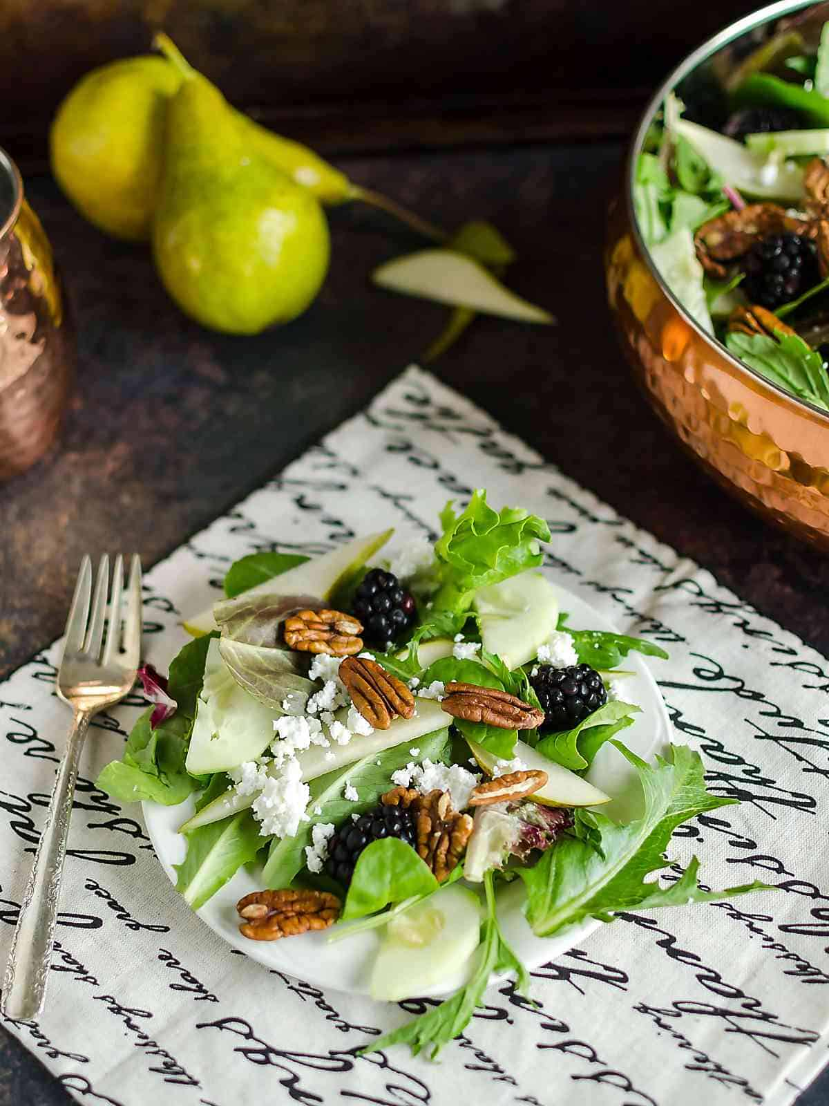 Mixed Greens Salad Recipe ~ a plate full of mixed green salad recipe that contains field greens, fresh pear slices, black berries, crumbled white cheese and pecan halves, bowl of salad in the background and 2 full pears