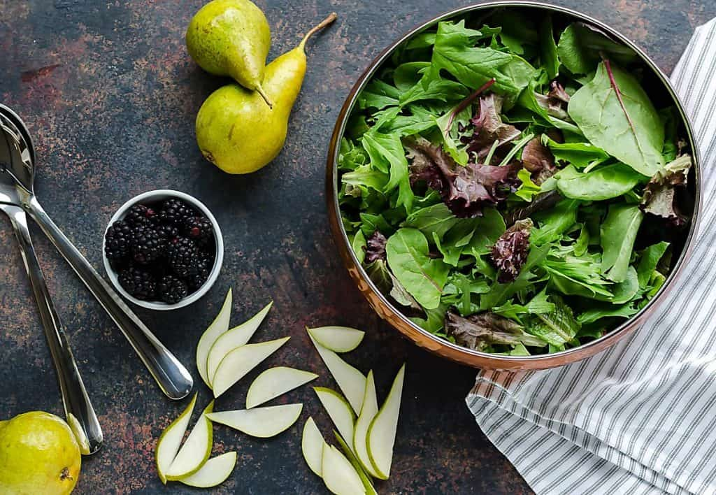 copper bowl of mixed greens, fresh pear slices on the table beside the bowl, small round container of fresh blackberries, 2 whole pears
