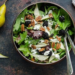 Mixed greens salad in a copper bowl full of mixed field greens, fresh pear slices, blackberries, pecans and crumbled goat cheese. 2 whole pears sitting beside it with a few pear slices