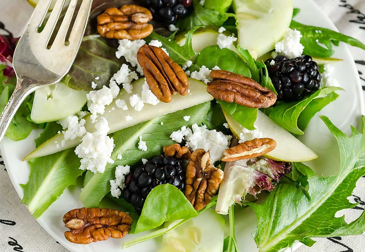 mixed greens, pear slices, blackberries, pecans and crumbled cheese with a fork resting on top