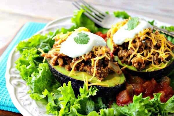 avocado halves stuffed with turkey taco meet topped wiht cheese and sour cream for your october meal plan week 3