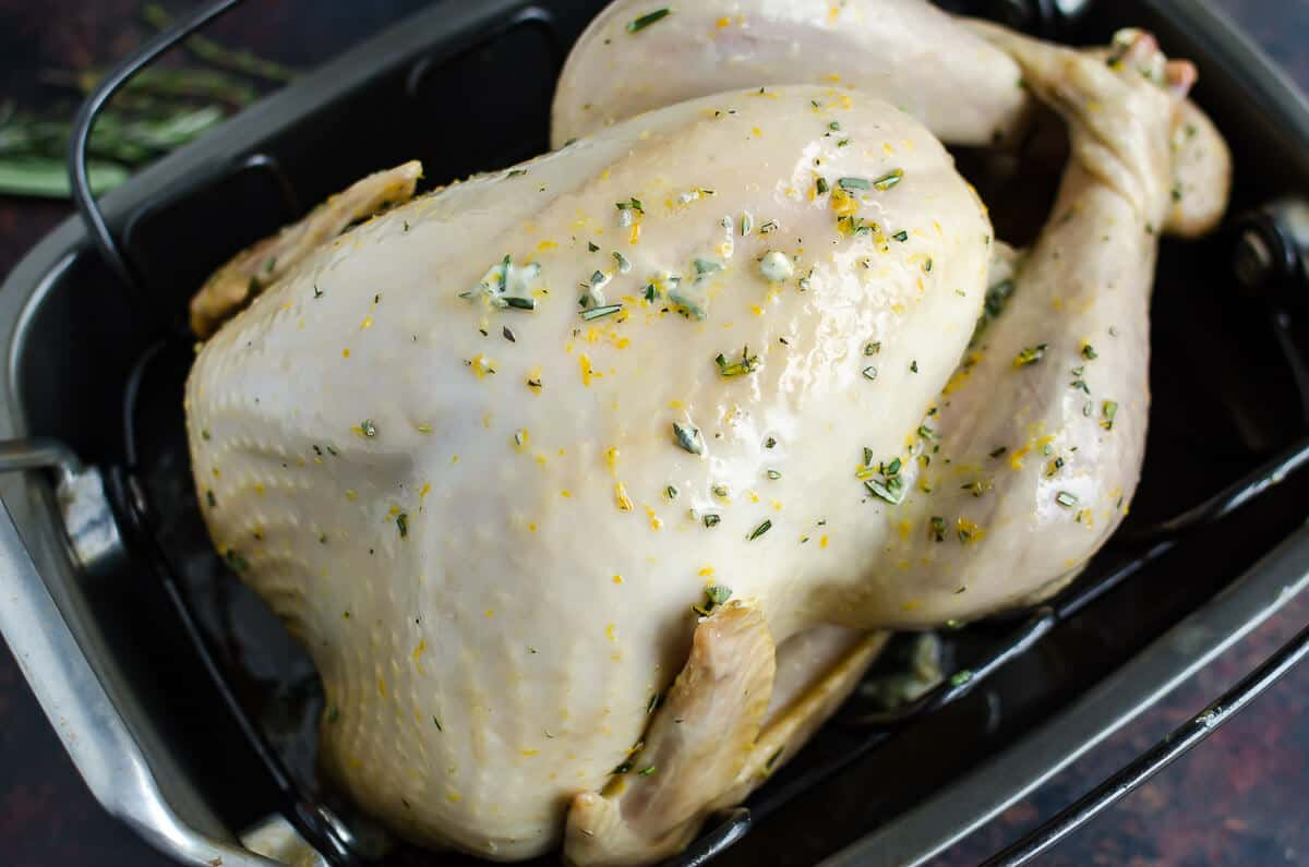 partially cooked whole turkey in a roasting pan with herbed butter gradually melting in to the skin.