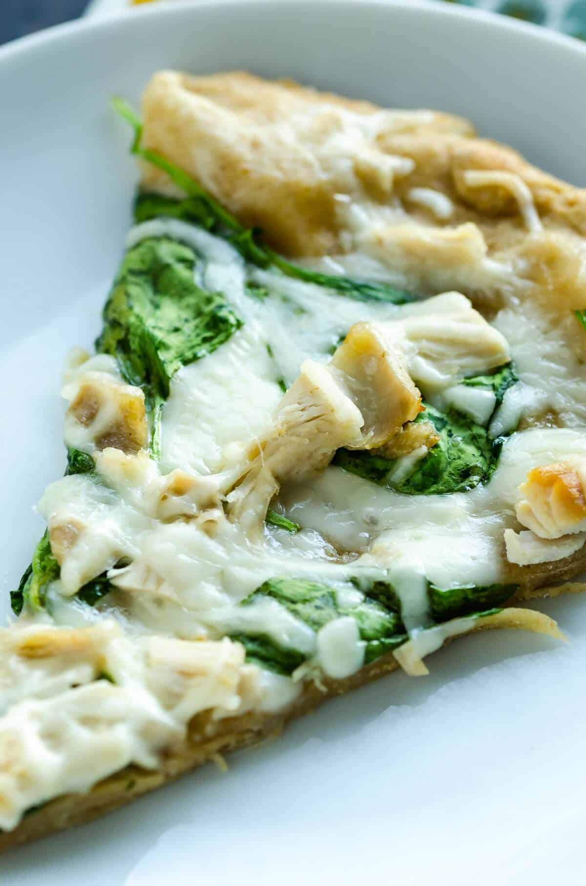 slice of hot homemade white pizza, melty cheese, chunks of chicken and spinach leaves