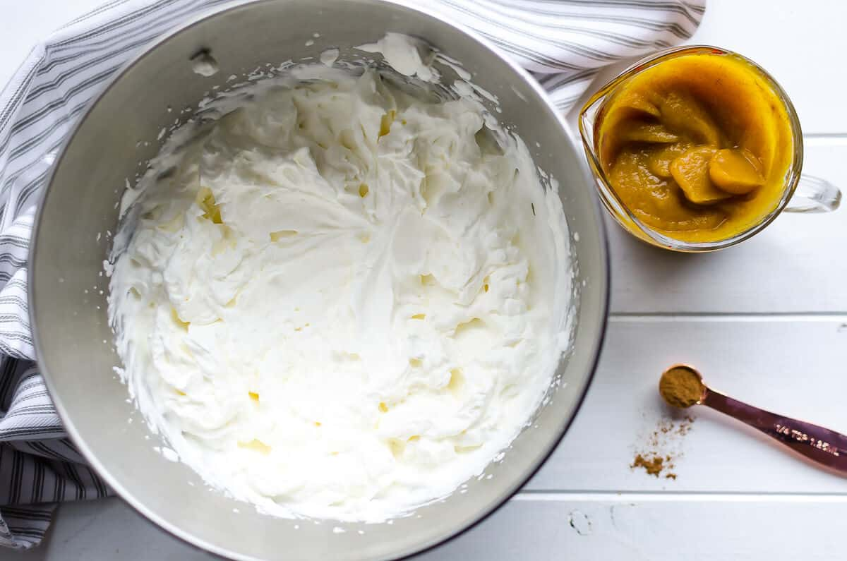 bowl of whipped cream, cup of pumpkin puree, teaspoon of pumpkin pie spice