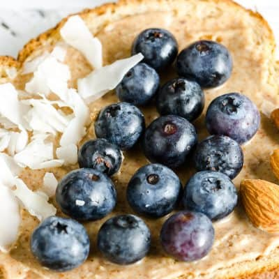 whole grain toast topped with almond butter, section of coconut flakes, section of fresh blueberries, section of almonds