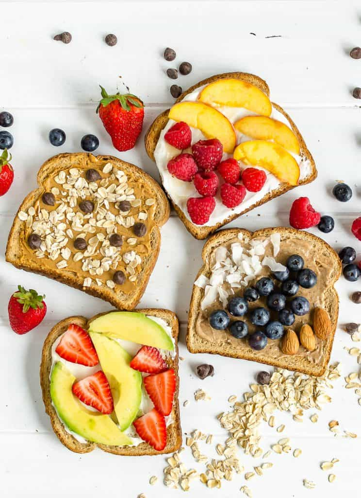 4 breakfast toast ideas, 1 slice with peanut butter, rolled oats and chocolate chips, 1 with yogurt, honey, fresh raspberries and fresh peaches, 1 with almond butter, coconut and fresh blueberries, 1 with cream cheese, avocado slices, and sliced strawberries