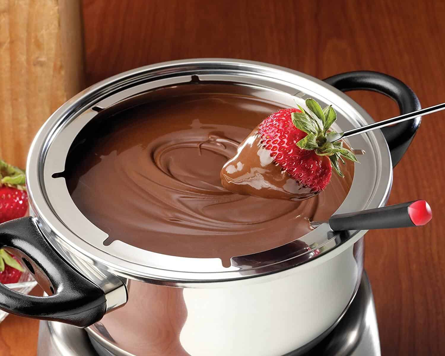 fondue pot full of chocolate fondue with a strawberry being dipped in