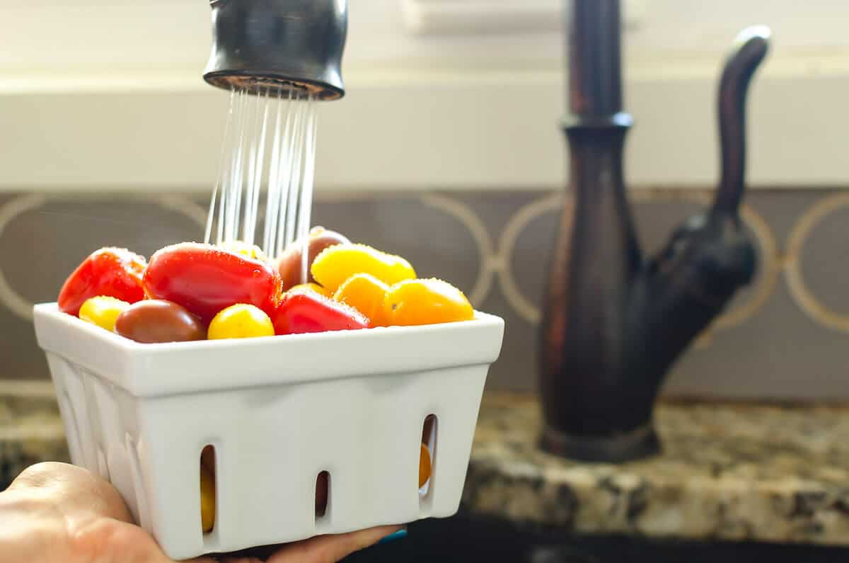 quart of red, orange, and yellow grape sized tomatoes being held under a faucet of running water.