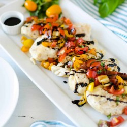 rectangle white platter with tender chicken breasts topped with marinated tomatoes, basil, and garlic and topped with balsamic vinegar drizzle. Instant Pot Bruschetta Chicken