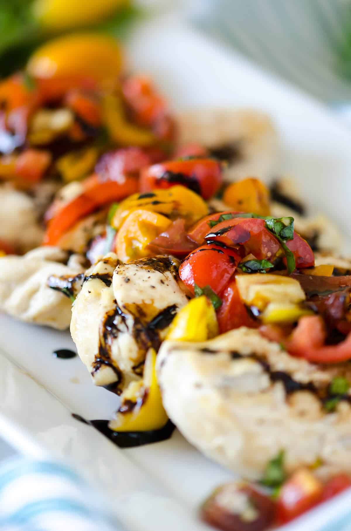 Chicken breasts topped with red, orange and yellow tomatoes and fresh basil marinated in olive oil and balsamic vinegar