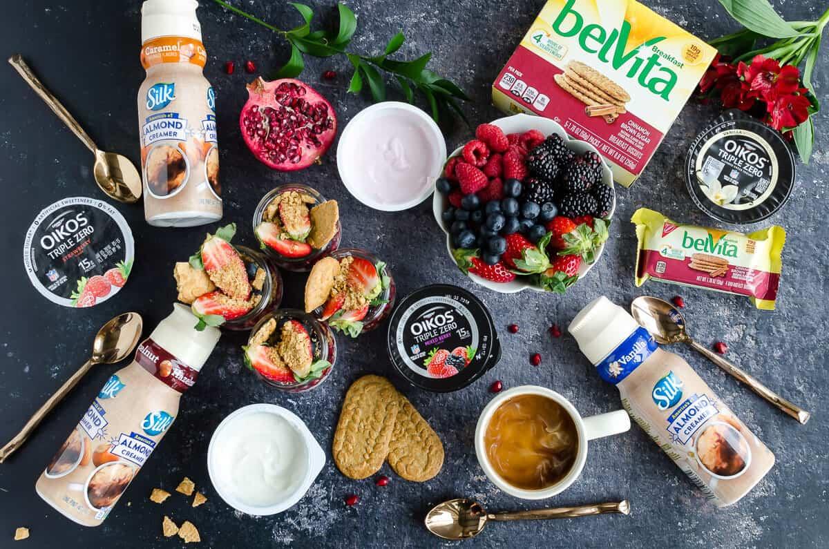breakfast spread overhead view of silk creamers, breakfast chia pudding, fresh berries, belVita breakfast biscuits, Oikos triple zero yogurt, coffee cup with cream, gold spoons