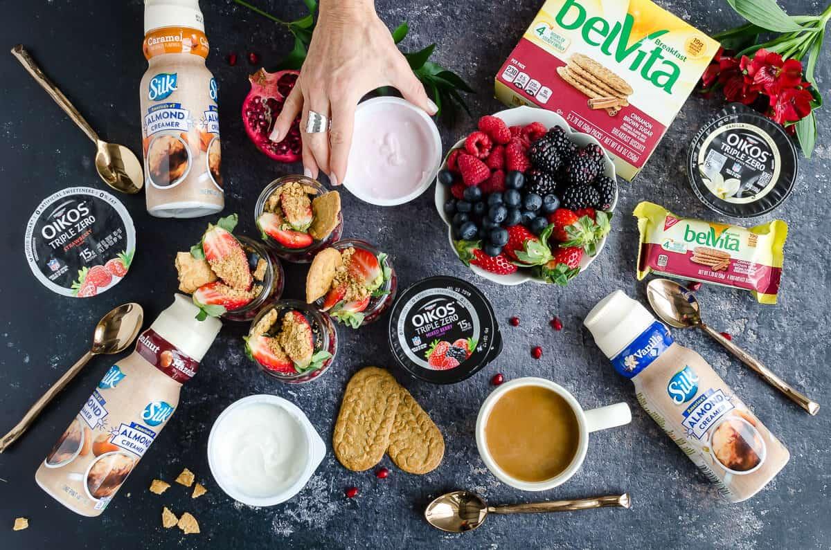 breakfast spread overhead view of silk creamers, breakfast chia pudding, fresh berries, belVita breakfast biscuits, Oikos triple zero yogurt, coffee cup wiht cream, hand reaching in grabbing yogurt, gold spoons