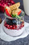 glass jar layered with chia seed pudding, pomegranate arils, blackberries, blueberries, strawberries, and crumbled belVita breakfast biscuit